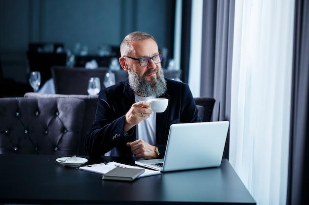 Biznesmen dorosły mężczyzna pracuje nad nowym projektem i patrzy na wykresy giełdowe. siedzi przy stole z kawą. patrzy na ekran laptopa i pije kawę.