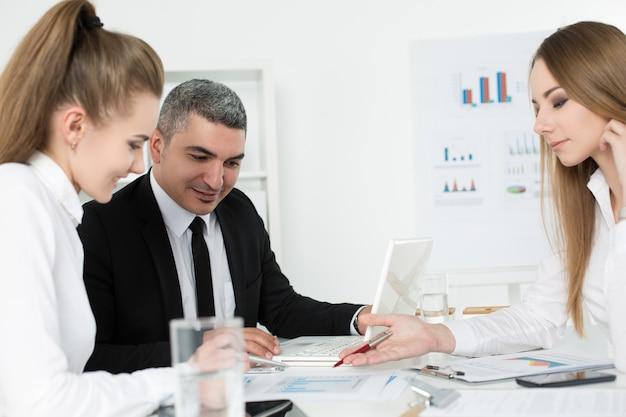 Biznesmen dorosłych konsultacji z młodymi koleżankami płci żeńskiej podczas spotkania biznesowego. partnerzy omawiający dokumenty i pomysły