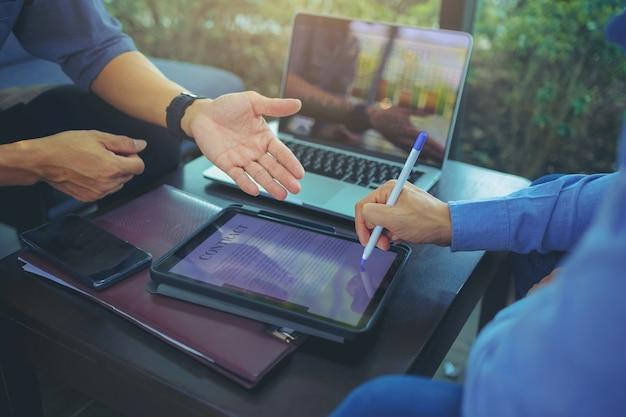 Biznesmen dostał cyfrowy ołówek do złożenia podpisu na cyfrowej umowie na spotkaniu biznesowym po negocjacjach z partnerami biznesowymi