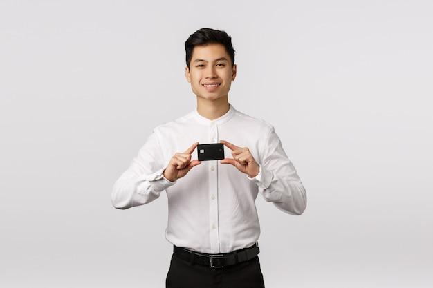 Biznesmen dostał nową kartę kredytową. zadowolony przystojny azjatycki młody człowiek trzyma kartę bankową i uśmiecha się zadowolony, zapłaci gotówką, otrzyma bonusy, wprowadzi produkt finansowy,
