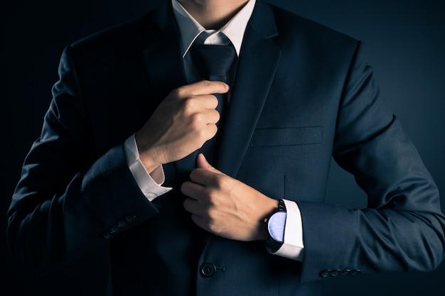 Biznesmen dostosowuje krawat jego garnitur