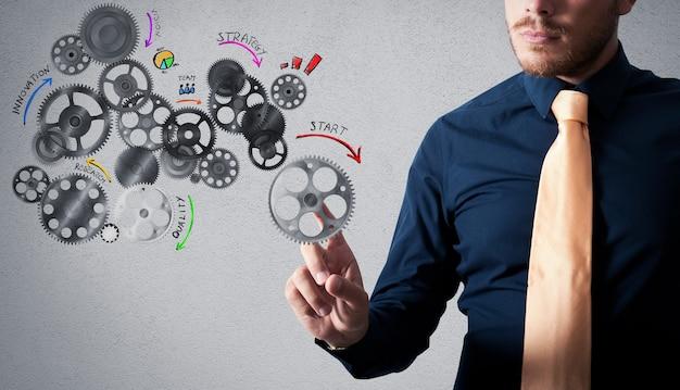 Biznesmen dotknięcie projektu analizy z zaprojektowanymi mechanizmami przekładni
