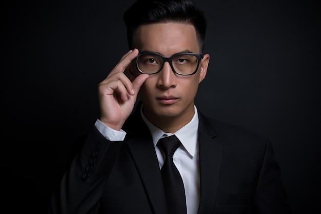 Biznesmen dotyka jego okularów