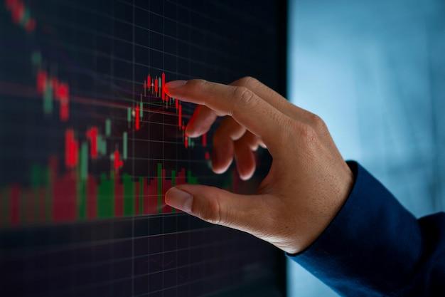 Biznesmen dotyka wykresu świecznika z rynku akcji