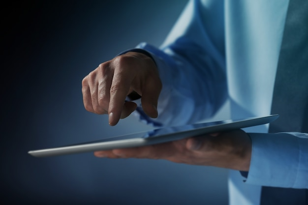 Biznesmen dotykając ekranu nowoczesnego tabletu, zbliżenie