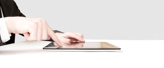 Biznesmen dotykając palcem ekranu cyfrowego tabletu przy bramie odlotów lotniska