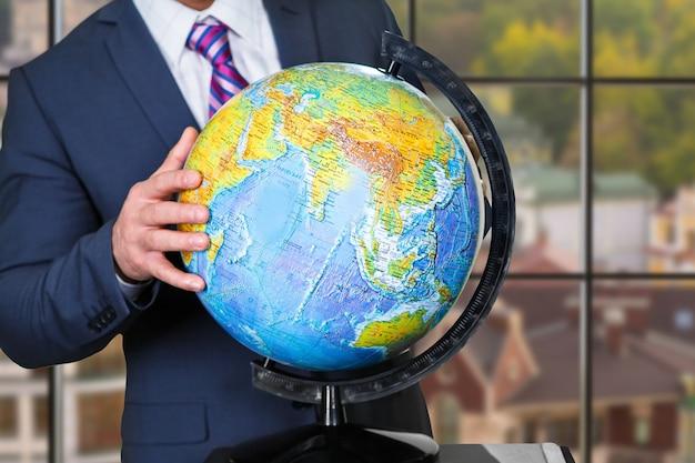 Biznesmen dotykając świata ręką. globus na tle miejskim. nauczyciel geografii w pracy. planeta w miniaturze.