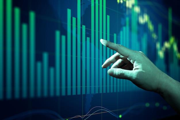 Biznesmen dotykając wykresów i diagramów rynku akcji na pokładzie.