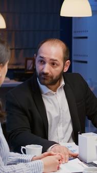 Biznesmen dyskutujący z ukierunkowaną, różnorodną, wieloetniczną pracą zespołową, rozwiązującą statystyki firmy