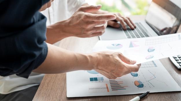 Biznesmen dyskutuje wyjaśniać nowe trendy informacje na dokumencie z kolegi współpracownikiem