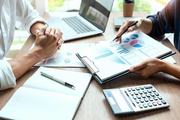 Biznesmen dyskutuje wyjaśnianie informacji o nowych trendach na dokumencie razem ze współpracownikiem lub partnerem w nowoczesnym biurze firmy.
