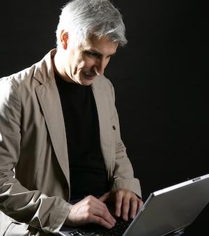 Biznesmen działający laptop, starszy siwy włosy