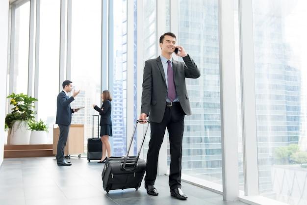 Biznesmen dzwoni na telefonie komórkowym przy budynku biurowego korytarzem z bagażem