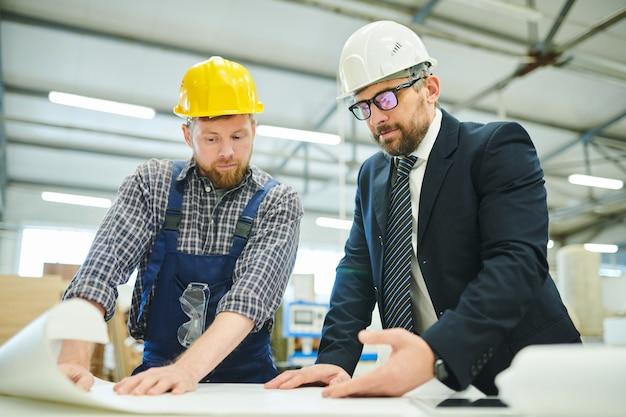 Biznesmen egzamininuje nakreślenie z inżynierem