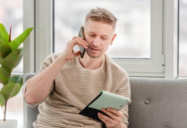 Biznesmen freelancer człowiek rozmawia przez telefon i trzymając w rękach notatnik