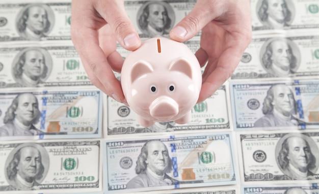 Biznesmen gospodarstwa piggy bank na tle dolarów inwestycje