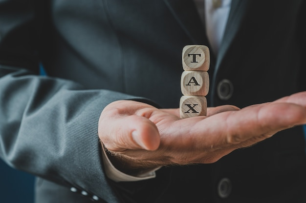 Biznesmen gospodarstwa skumulowane drewniane kostki pisowni podatek w dłoni.