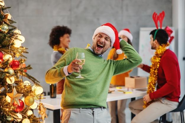 Biznesmen gospodarstwa szampana stojąc obok choinki w jego firmie w wigilię bożego narodzenia.