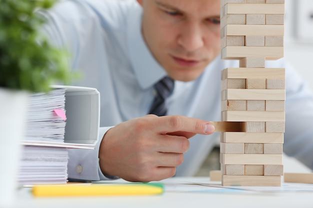 Biznesmen gra w strategię ręki jenga