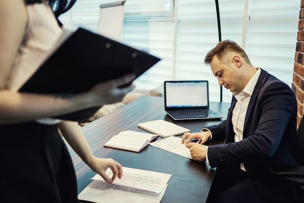 Biznesmen i asystent sekretarza w swoim biurze przynieśli dokumenty szefa do podpisu