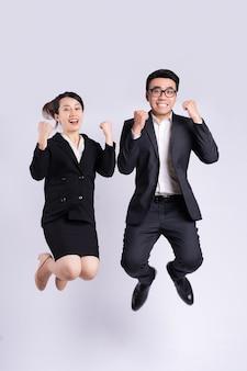 Biznesmen i biznesowa kobieta skaczą na białym tle