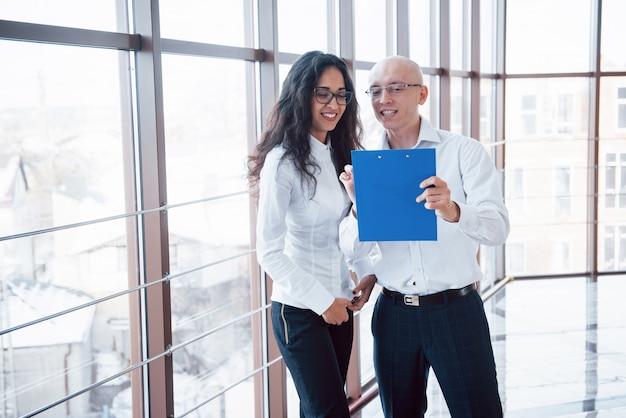 Biznesmen i biznesowa kobieta studiuje mapę na talerzu i papierowych dokumentach przy okno na tle urzędu miasta na wysokiej podłoga