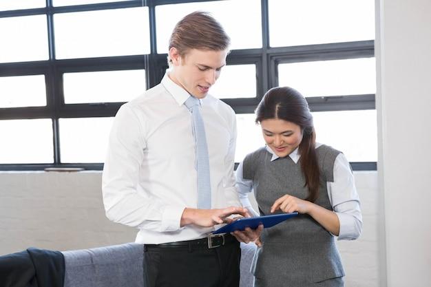 Biznesmen i bizneswoman oddziała wzajemnie używać cyfrową pastylkę w biurze
