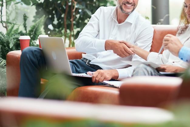 Biznesmen i bizneswoman podają sobie ręce podczas spotkania