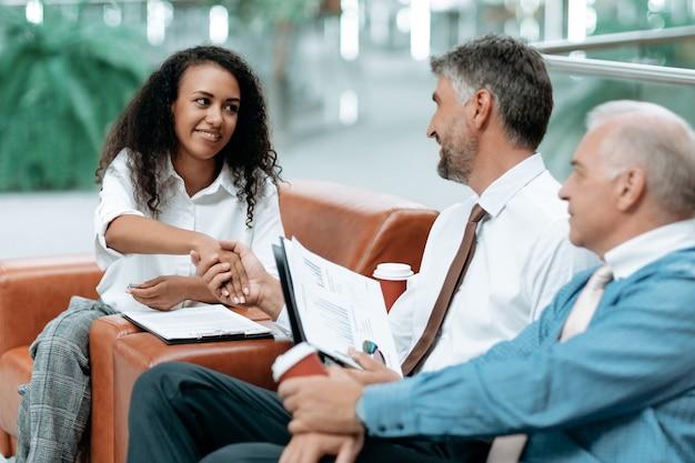 Biznesmen i bizneswoman podają sobie ręce przed spotkaniem