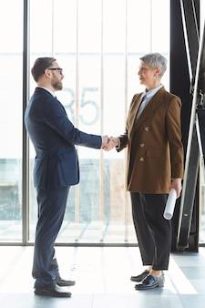Biznesmen i bizneswoman pozdrawiają siebie w biurze, ściskając ręce