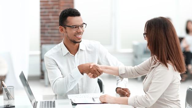 Biznesmen i bizneswoman robi transakcję w nowoczesnym biurze. koncepcja partnerstwa