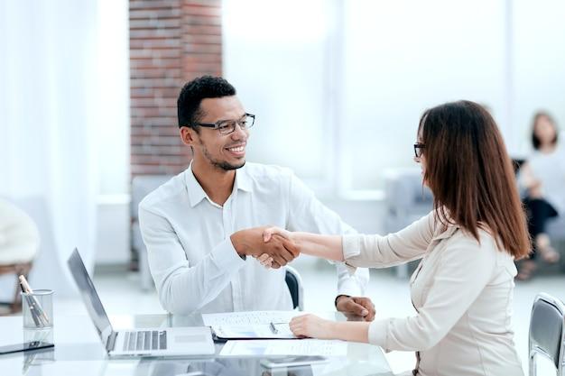 Biznesmen i bizneswoman robi transakcję w nowoczesnym biurze