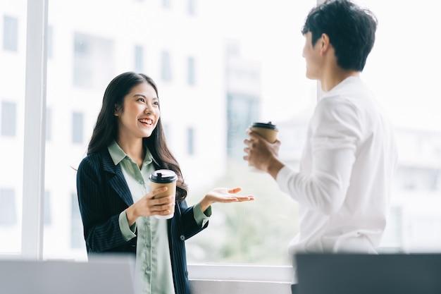 Biznesmen i bizneswoman rozmawiają ze sobą podczas przerwy obiadowej