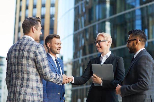 Biznesmen i bizneswoman, ściskając ręce i witając się, stojąc w mieście na świeżym powietrzu ze swoimi kolegami