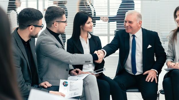 Biznesmen i bizneswoman uścisk dłoni w sali konferencyjnej. pomysł na biznes