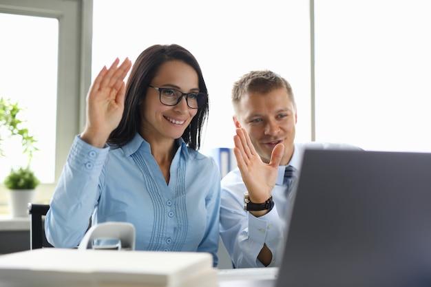Biznesmen i bizneswoman w biurze witają rozmówcę za pośrednictwem komunikacji wideo.