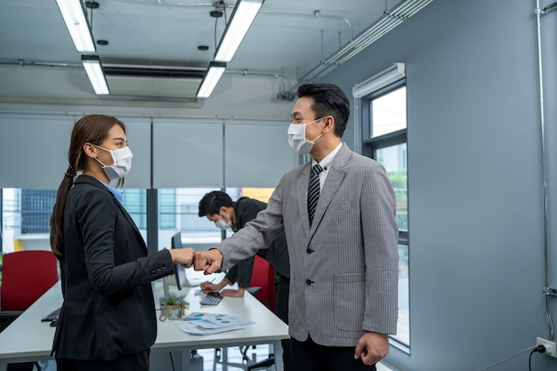Biznesmen i bizneswoman z maską medyczną w biurze po kwarantannie i zamknięciu covid-19.