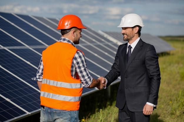 Biznesmen i brygadier drżenie rąk na stacji energii słonecznej.