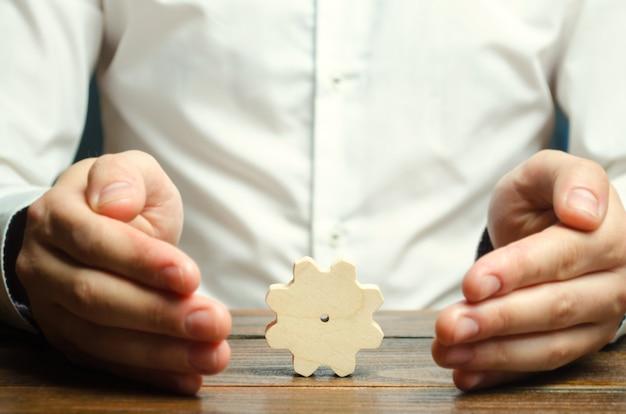 Biznesmen i drewniana przekładnia. zakładanie biznesu