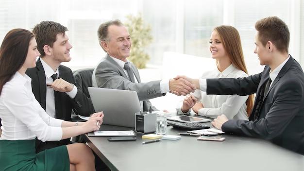 Biznesmen i inwestor podają sobie ręce przy stole negocjacyjnym w biurze