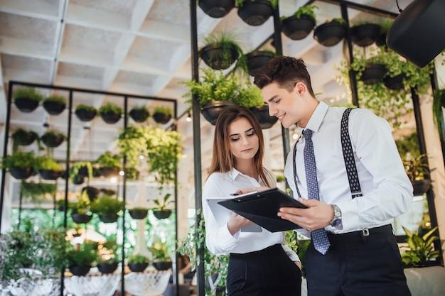 Biznesmen i jego asystentka w białych koszulach w nowoczesnym biurze przeglądają dokumenty i omawiają pracę