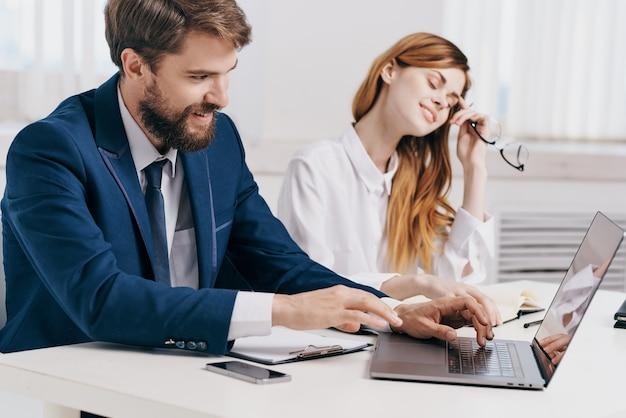Biznesmen i kobieta siedzą przy stole przed laptopem w technologii biurowej