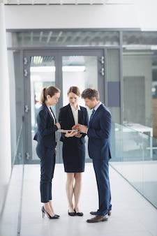 Biznesmen i kolega, rozmawiając przez cyfrowy tablet