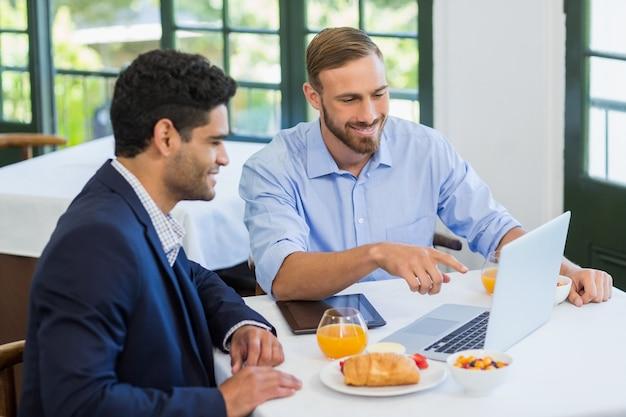 Biznesmen i kolega używa laptop