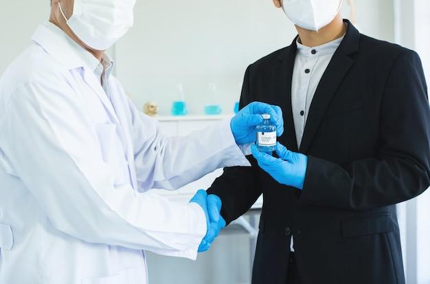 Biznesmen i lekarz ściskają rękę za zgodą szczepionki covid19 w dłoni.
