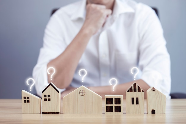 Biznesmen i mały model domu ze znakiem zapytania