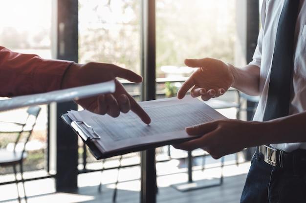 Biznesmen i partnerzy dyskutują o znalezieniu wniosku na giełdzie