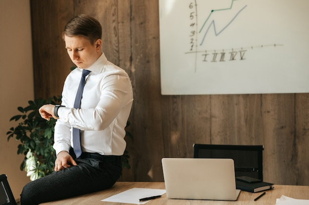 Biznesmen i pracownik biurowy mężczyzna siedzi przy biurku w swoim biurze i obserwuje czas na swoim zegarku.