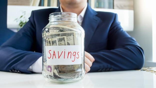 Biznesmen i słoik za pieniądze pełne banknotów dolarowych. koncepcja inwestycji finansowych, wzrostu gospodarczego i oszczędności bankowych.