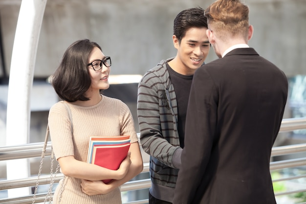 Biznesmen i studenci collegu dyskutuje edukację